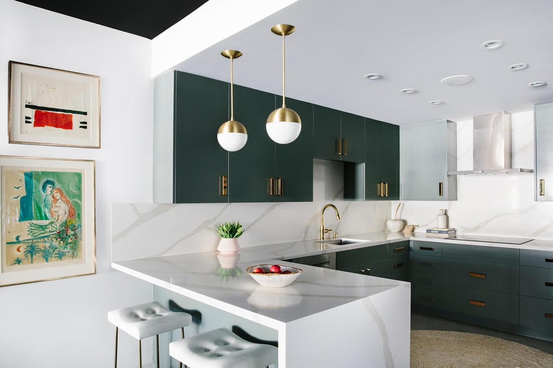 آشپزخانه ای بزرگ با صفحه کابینت کورین سفید رنگ با رگه های تیره